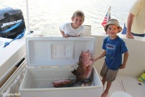 2 boys with cooler of fish