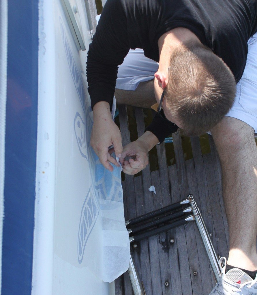 Our boat lettering installer applying the turtle to our trawler