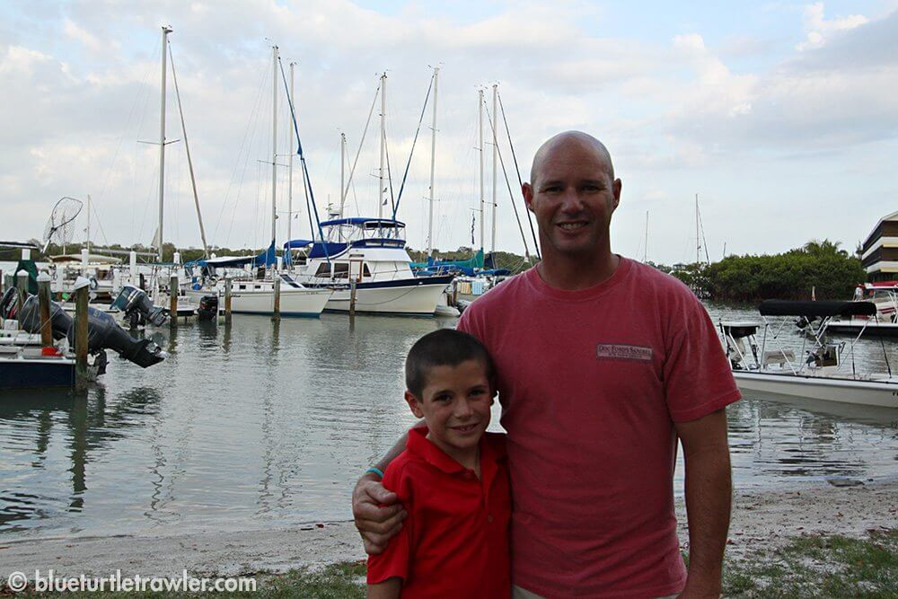 Randy and Corey with blue Turtle and lots of sailboats behind them