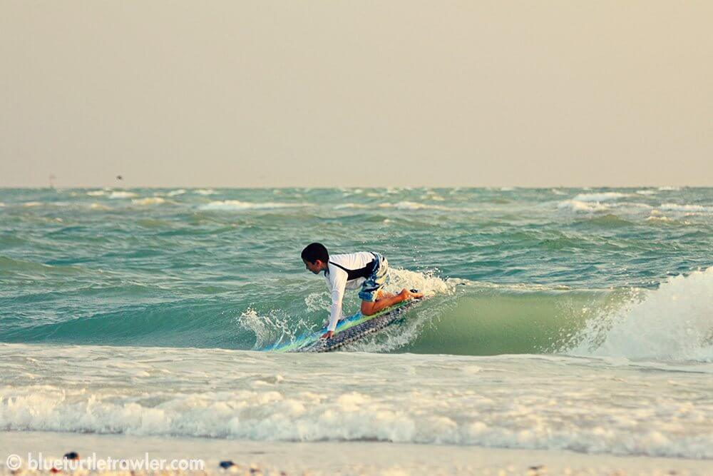 Corey gets up on a wave on his surf board