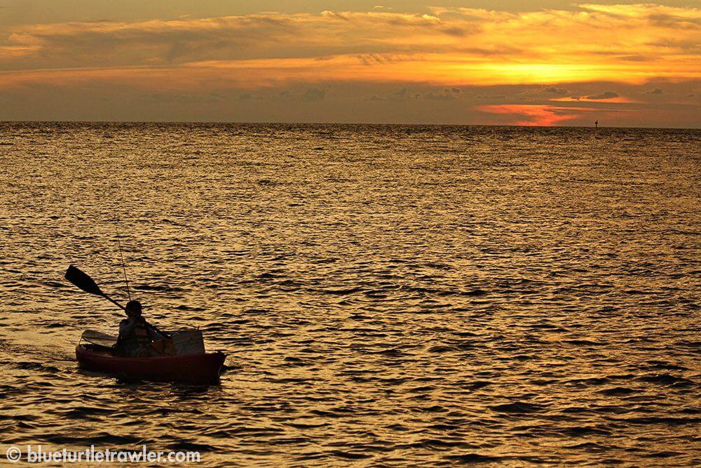 Corey paddles his kayak at sunset