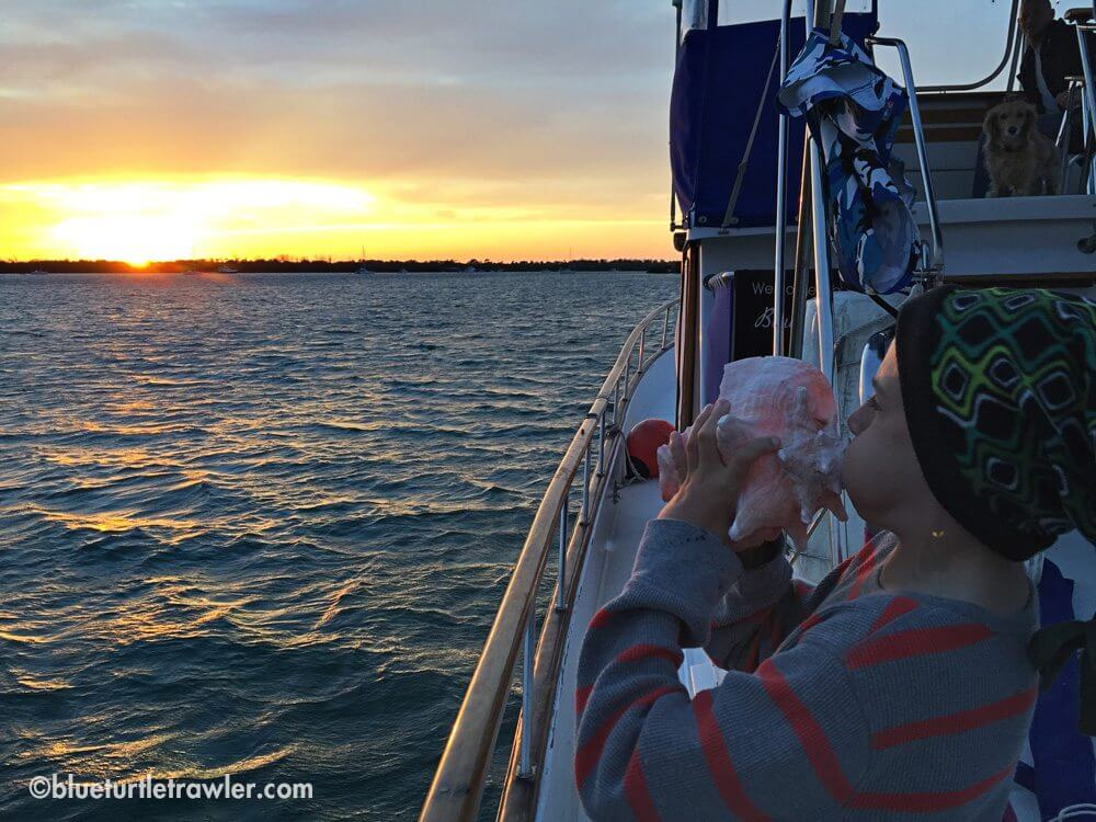 Corey blows the conch horn to signify the sun setting