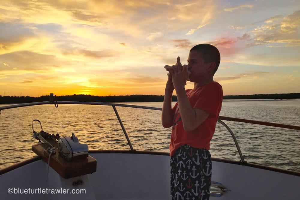 Corey blows the conch at sunset, New Pass