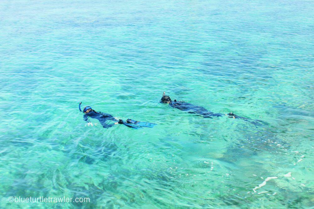 The boys begin their snorkel in crystal clear water