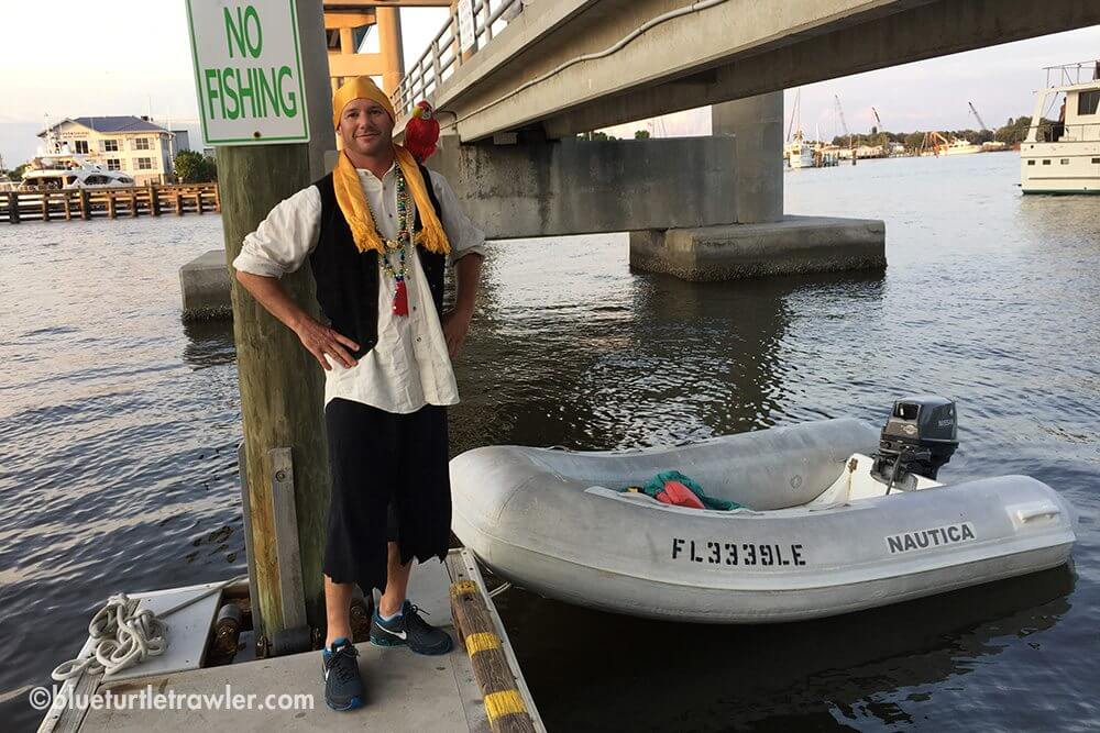 Randy at the dinghy dock with his pet parrot, Tiki