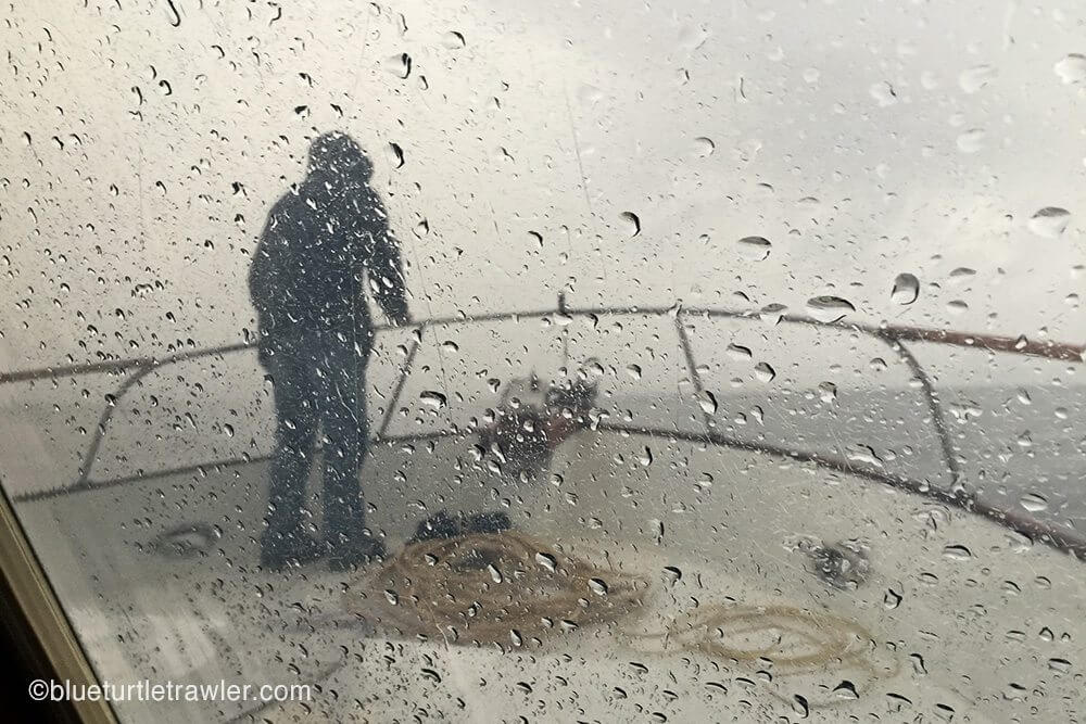 Randy anchors the boat in the rain and we wait it out