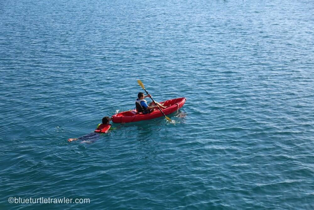 Corey paddles and Matt swims the kayak to shore