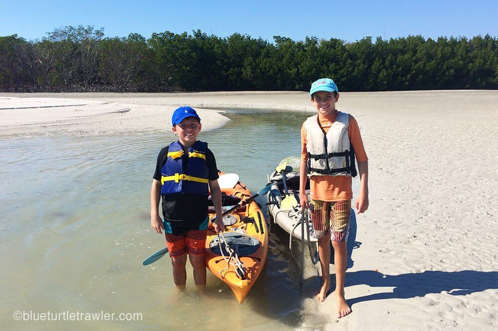 two boys and kayaks at beach