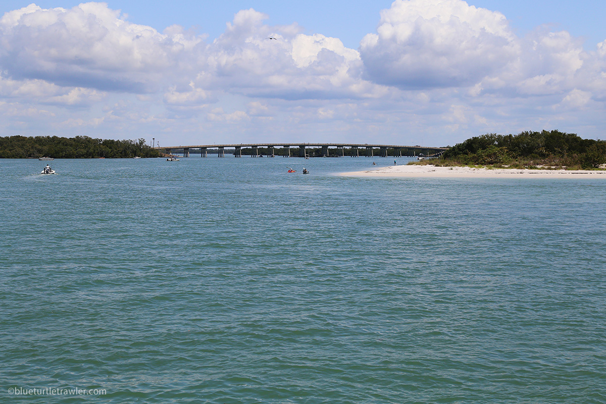 water and beach with New Pass bridge in background